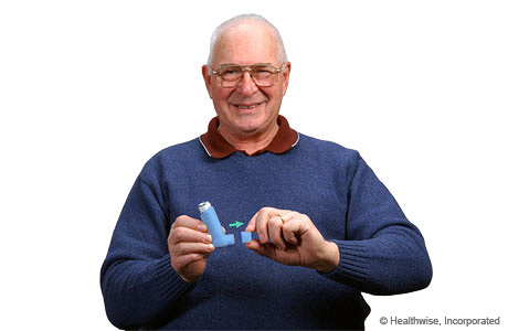 A man removing the cap from an inhaler