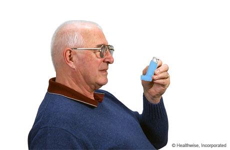 Un hombre sosteniendo el inhalador en posición vertical