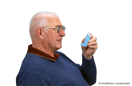 A man holding the inhaler upright
