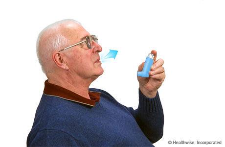 Un hombre inclinando la cabeza hacia atrás y exhalando