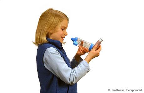 A child holding the inhaler upright