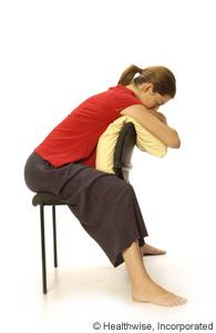 Una mujer sentada al revés en una silla y apoyándose sobre una almohada
