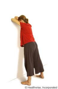 Una mujer inclinándose hacia adelante contra una pared