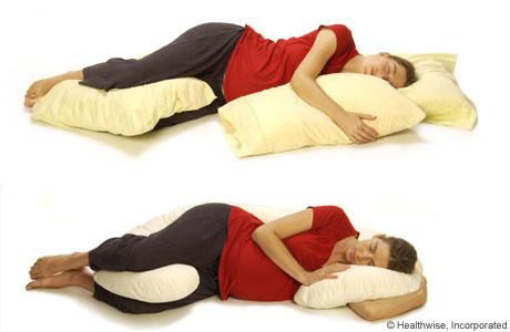 Una mujer embarazada recostada de lado y apoyándose sobre almohadas