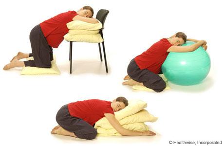 Mujer de rodillas apoyándose sobre almohadas y una pelota de nacimiento