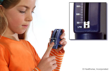 A child setting a peak flow meter to its lowest number