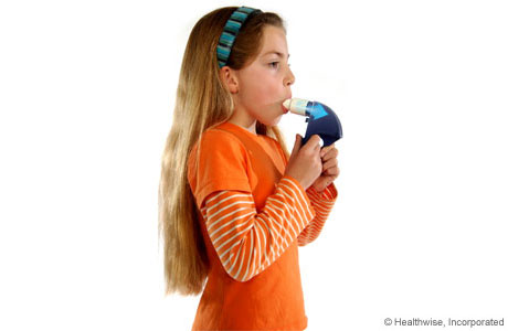 A child breathing out hard into the peak flow meter