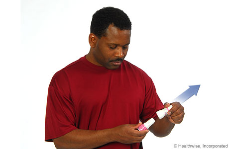 A man removing the cap from the inhaler