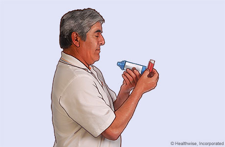 Picture of a man holding the inhaler upright