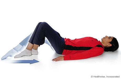 Una mujer haciendo un ejercicio de flexión de rodillas con deslizamiento de talón