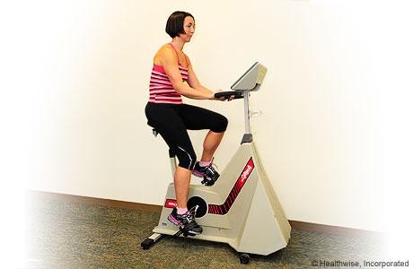 Una mujer haciendo ejercicio en una bicicleta fija