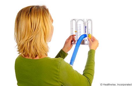 Una mujer sosteniendo el espirómtero nivelado y hacia afuera delante de su cara