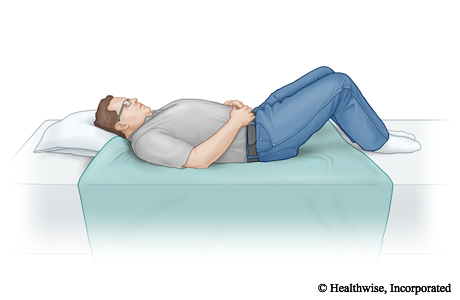 A sheet folded in half and placed on the bed between where the person's knees and head will be