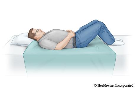 Una sábana doblada por la mitad y colocada en la cama en el lugar entre el que estarán las rodillas y la cabeza de la persona