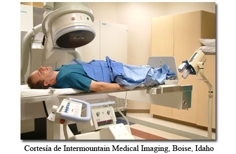 Una persona recostada debajo de una máquina de rayos X en un laboratorio de cateterismo cardíaco