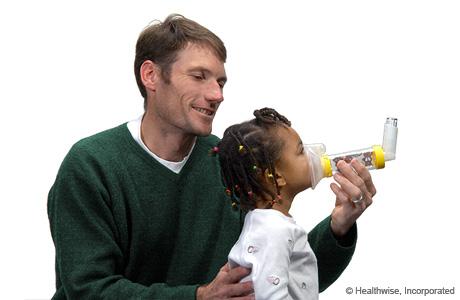 Colocar el espaciador con mascarilla sobre la boca y la nariz del niño