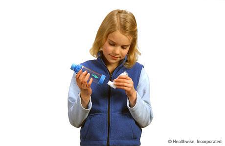 Una niña colocando la boquilla del inhalador en el espaciador