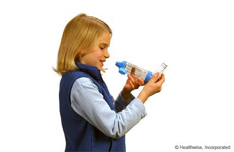 Una niña sosteniendo el inhalador en posición vertical