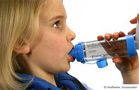 Una niña colocando la boquilla del espaciador en su boca