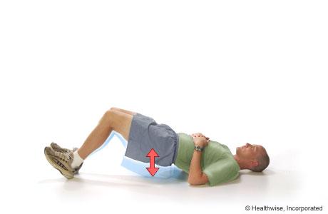 Un hombre realizando el ejercicio de puente sostenido con los talones