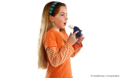 Una niña respirando hondo antes de usar el medidor de flujo máximo
