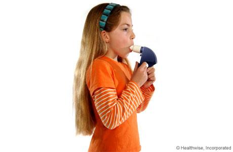 Una niña colocándose la boquilla del medidor de flujo máximo en la boca